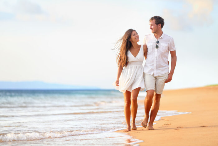 27539928 - beach couple walking on romantic travel honeymoon vacation summer holidays romance. young happy lovers, asian woman and caucasian man holding hands embracing outdoors.